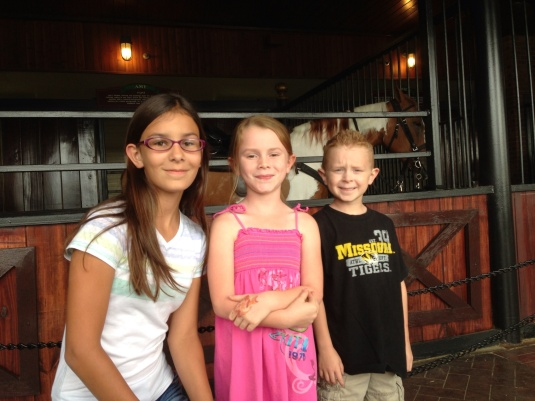 (L to R) Jade, Kylee, and Jackson looking at the horses in their stables before the show