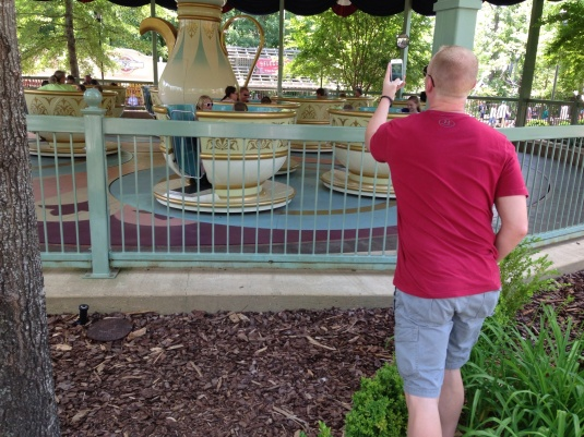 This is a picture of Dad taking a picture of his kids on the Tea Cup ride.