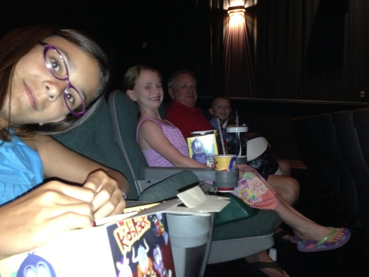 Waiting for the movie to begin.  Kylee didn't touch one piece of popcorn until it began.